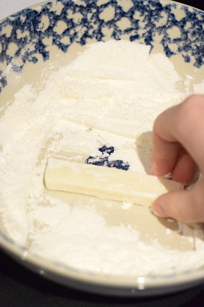 rolling mozzarella in coconut flour